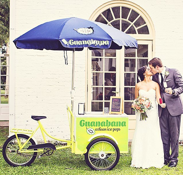 newlyweds standing next to ice pop tricycle during cocktail hour