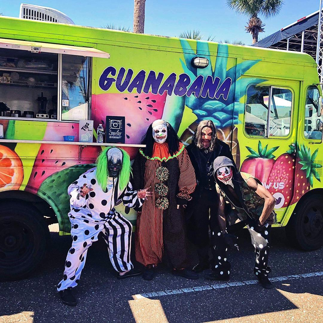 people with costumes in from of food truck